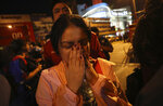 A woman who was able to get out of Terminal 21 Korat mall gestures with her hands on her face in Nakhon Ratchasima, Thailand on Sunday, Feb. 9, 2020. A soldier who holed up in a popular shopping mall in northeastern Thailand shot multiple people on Saturday, killing at least 20 and injuring 31 others, officials said. (AP Photo/Sakchai Lalitkanjanakul)