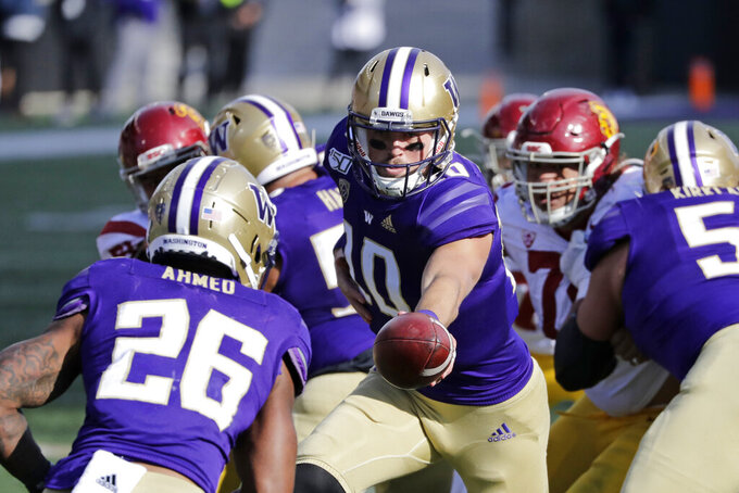 Washington quarterback Jacob Eason (10) hands-off to Salvon Ahmed against Southern Cal in the second half of an NCAA college football game Saturday, Sept. 28, 2019, in Seattle. Washington won 28-14. (AP Photo/Elaine Thompson)