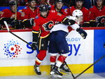 Florida Panthers' Jayce Hawryluk, right, checks Calgary Flames' Oliver Kylington, of Sweden, during second-period NHL hockey game action in Calgary, Alberta, Friday, Jan. 11, 2019. (Jeff McIntosh/The Canadian Press via AP)