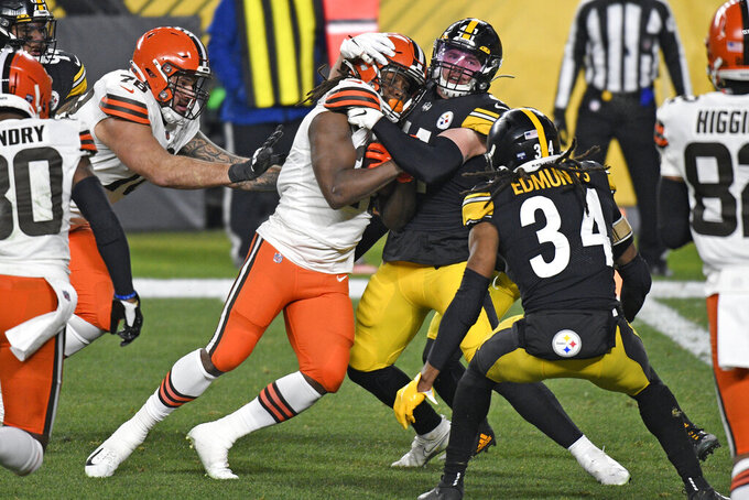 Cleveland Browns running back Kareem Hunt, left, center, pushes his way into the end zone for a touchdown with Pittsburgh Steelers inside linebacker Robert Spillane (41) defending on an 11-yard run during the first half of an NFL wild-card playoff football game in Pittsburgh, Sunday, Jan. 10, 2021. (AP Photo/Don Wright)