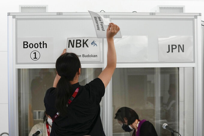 Interpreters work at the main press center during the 2020 Summer Olympics, Friday, July 30, 2021, in Tokyo, Japan. Unlike previous Olympics, all the interpretation is being done remotely with most interpreters working in booths at the main center. Their simultaneous translation can be accessed at all Olympic venues on an app. This eliminates interpreters getting tied up in traffic heading to an venue. (AP Photo/Luca Bruno)