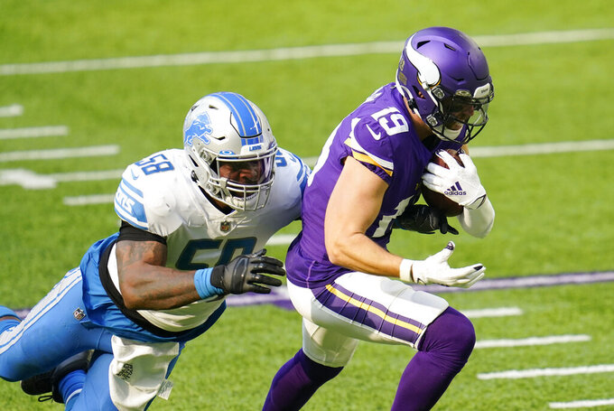 Minnesota Vikings wide receiver Adam Thielen tries to break a tackle by Detroit Lions linebacker Jamie Collins Sr. (58) during the first half of an NFL football game, Sunday, Nov. 8, 2020, in Minneapolis. (AP Photo/Jim Mone)