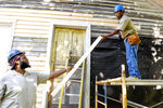In this Thursday, May 2, 2019 photo, Sanquan McNair, left, hands a siding board to fellow Job Corps student Smith Tucker as they work on restoring Nina Simone's birthplace in Tryon, N.C. The nearly 90-year-old home where Simone grew up in Tryon, north of the city's downtown, is being stabilized after years of neglect that nearly saw the structure be demolished. Workers from the National Trust for Historic Preservation's HOPE Crew plan to spend much of May replacing and painting exterior siding on the 660-square-foot structure ahead of additional work on windows, interior and the roof. (Angela Wihelm/The Asheville Citizen-Times via AP)