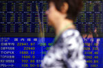 A woman walks past an electronic stock board showing Japan's Nikkei 225 index at a securities firm Thursday, Nov. 21, 2019, in Nagoya, central Japan. Shares skidded Thursday in Asia after moderate declines on Wall Street as anxious mounted over the possibility the U.S. and China may not reach a trade deal before next year. (AP Photo/Eugene Hoshiko)