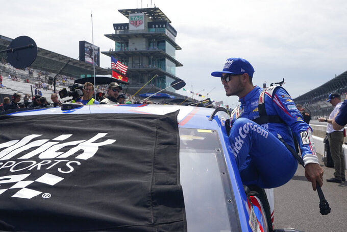 Kyle Larson climbs into his car before a NASCAR Series auto race at Indianapolis Motor Speedway, Sunday, Aug. 15, 2021, in Indianapolis. (AP Photo/Darron Cummings)