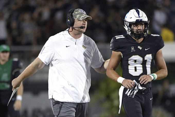 Central Florida head coach Josh Heupel, left, gives instructions to wide receiver Alex Harris (81) during the first half of an NCAA college football game against Connecticut, Saturday, Sept. 28, 2019, in Orlando, Fla. (AP Photo/Phelan M. Ebenhack)