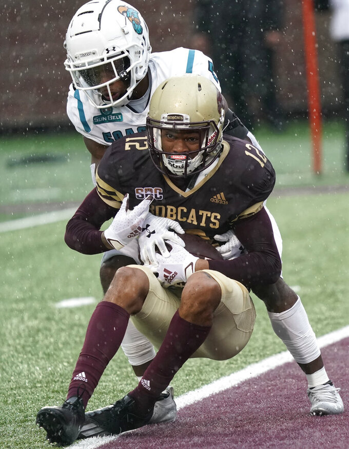 Texas State's Javen Banks (12) catches a touchdown pass as Coastal Carolina's D'Jordan Strong (7) defends during the first half of an NCAA college football game in Austin, Texas, Saturday, Nov. 28, 2020. (AP Photo/Chuck Burton)