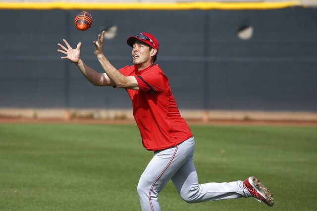 Cincinnati Reds center fielder Shogo Akiyama, of Japan, reaches up to catch a football as outfielders warm up during spring training baseball workouts Friday, Feb. 21, 2020, in Goodyear, Ariz. (AP Photo/Ross D. Franklin)
