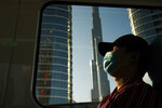 FILE - In this April 26, 2020 file photo, a commuter wearing a face mask to help curb the spread of the coronavirus, sleeps aboard the driverless Metro as it passes the Burj Khalifa, the world's tallest building, in Dubai, United Arab Emirates. Travel agencies in countries across the Middle East and Africa say the United Arab Emirates has temporarily halted issuing new visas to their citizens, a so-far unexplained ban on visitors amid both the coronavirus pandemic and as the UAE normalizes ties with Israel. (AP Photo/Jon Gambrell, File)