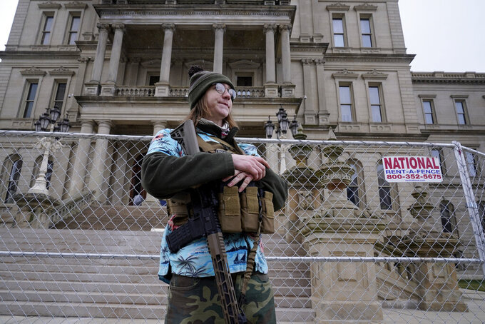 Timothy Teagan, a member of the Boogaloo Bois movement, stands with his rifle outside the state capitol in Lansing, Mich., Sunday, Jan. 17, 2021. (AP Photo/Paul Sancya)