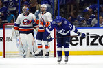 Tampa Bay Lightning left wing Alex Killorn (17) reacts as New York Islanders goaltender Semyon Varlamov (40) and defenseman Adam Pelech (3) celebrate their victory during Game 1 of an NHL hockey Stanley Cup semifinal playoff series Sunday, June 13, 2021, in Tampa, Fla. (AP Photo/Chris O'Meara)