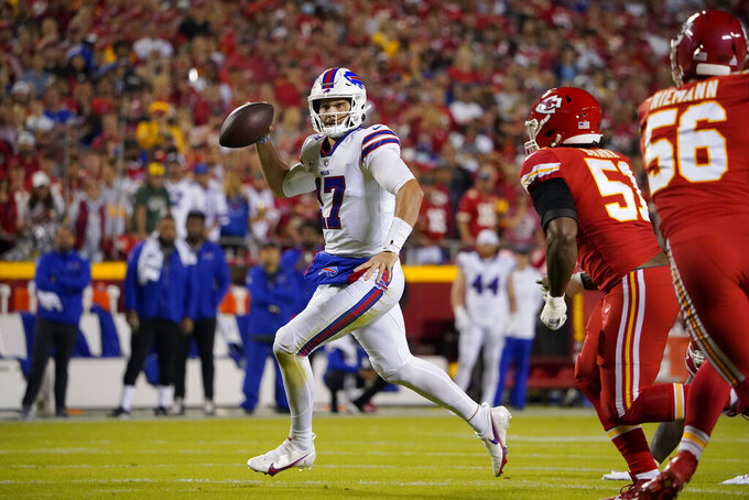 CORRECTS TO RUNS FOR A FIRST DOWN NOT A TOUCHDOWN - Buffalo Bills quarterback Josh Allen, left, runs for a first down as Kansas City Chiefs defensive end Mike Danna (51) defends during the first half of an NFL football game Sunday, Oct. 10, 2021, in Kansas City, Mo. (AP Photo/Ed Zurga)