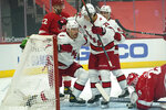 Carolina Hurricanes right wing Nino Niederreiter (21) celebrates his goal with Sebastian Aho (20) as Detroit Red Wings goaltender Thomas Greiss (29) looks at the puck in the first period of an NHL hockey game Thursday, Jan. 14, 2021, in Detroit. (AP Photo/Paul Sancya)