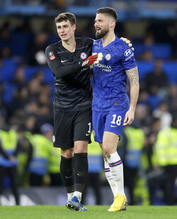 Chelsea's goalkeeper Kepa Arrizabalaga and Olivier Giroud, right, embrace following their 2-0 win in the English FA Cup fifth round soccer match between Chelsea and Liverpool at Stamford Bridge stadium in London Wednesday, March 4, 2020. (AP Photo/Kirsty Wigglesworth)