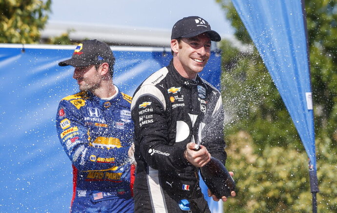 Simon Pagenaud, right, of France, celebrates in the Winner's Circle after taking first place at the Honda Indy auto race in Toronto, Sunday, July 14, 2019. (Mark Blinch/The Canadian Press via AP)