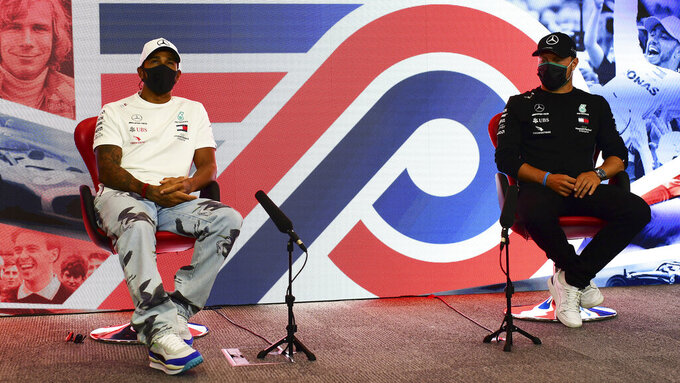 Lewis Hamilton of Great Britain and Mercedes GP and Valtteri Bottas of Finland and Mercedes GP talk in the Drivers Press Conference during previews ahead of the F1 Grand Prix of Great Britain at Silverstone on Thursday, July 30, 2020 in Silverstone, England. (AP Photo/Mario Renzi via Getty Images)