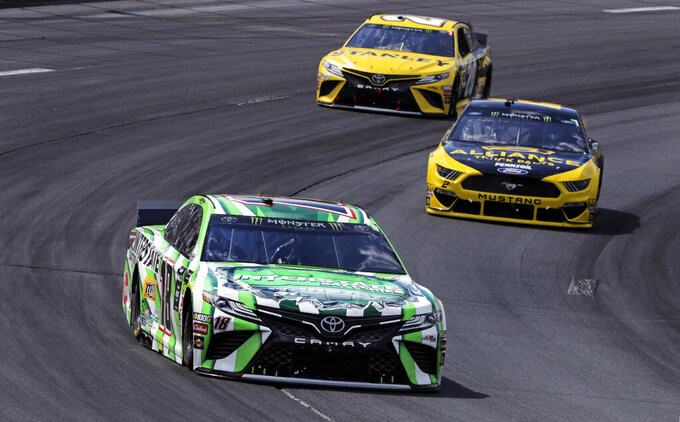 Kyle Busch (18) pulls ahead of pole sitter Brad Keselowski, right, and Erik Jones (20) during a NASCAR Cup Series auto race at New Hampshire Motor Speedway in Loudon, N.H., Sunday, July 21, 2019. (AP Photo/Charles Krupa)