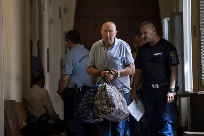 The 64-year-old Ukrainian captain of the Swiss-operated Viking Sigyn hotelship, centre, is escorted to a court hearing to decide on his arrest at the Buda Central District Court in Budapest, Hungary, Wednesday, July 31, 2019. On May 29, the Viking Sigyn cruise ship collided with the Hableany sightseeing boat that had 33 South Korean tourists on board and a crew of two Hungarians. Seven tourists were rescued from the water after the collision and the rest died. The captain was taken back into police custody on July 29 on suspicion of abandoning the passengers and crew of the Hableany sightseeing boat after the crash. (Marton Monus/MTI via AP)
