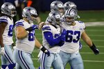 Dallas Cowboys' Brandon Knight (69) and Tyler Biadasz (63) walk off the field with running back Ezekiel Elliott (21) after Elliott fumbled the ball on a carry against the Arizona Cardinals in the first half of an NFL football game in Arlington, Texas, Monday, Oct. 19, 2020. (AP Photo/Ron Jenkins)