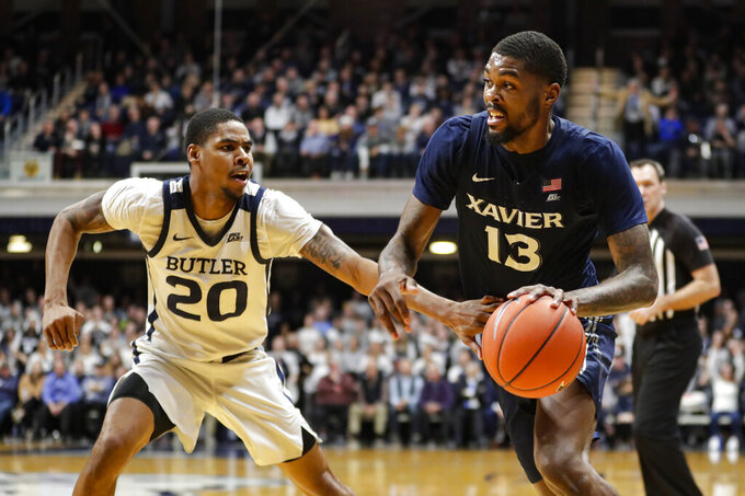 Xavier forward Naji Marshall (13) drives on Butler guard Henry Baddley (20) in the second half of an NCAA college basketball game in Indianapolis, Wednesday, Feb. 12, 2020. Butler defeated Xavier 66-61. (AP Photo/Michael Conroy)
