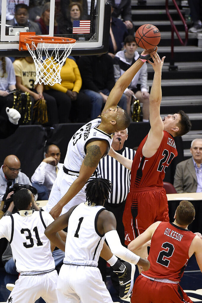 Wofford Terriers Cameron Jackson (33) stretches backwards to try to block a shot by VMI forward Tyler Creammer (25) in the first half of an NCAA college basketball game for the Southern Conference basketball tournament championship, Saturday, March 9, 2018, in Asheville, N.C. Wofford won 97-72. (AP Photo/Kathy Kmonicek)