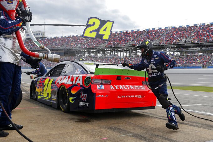 A crew member runs around the car as William Byron (24) gets a tire change during a NASCAR Cup Series auto race at Talladega Superspeedway, Monday, Oct 14, 2019, in Talladega, Ala. (AP Photo/Butch Dill)