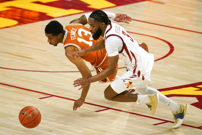 Texas guard Jase Febres (13) fights for a loose ball with Iowa State guard Tre Jackson (3) during the first half of an NCAA college basketball game, Tuesday, March 2, 2021, in Ames, Iowa. (AP Photo/Charlie Neibergall)