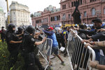 Soccer fans waiting to see Diego Maradona lying in state clash with police outside the presidential palace in Buenos Aires, Argentina, Thursday, Nov. 26, 2020. The Argentine soccer great who led his country to the 1986 World Cup title died Wednesday at the age of 60. (AP Photo/Rodrigo Abd)