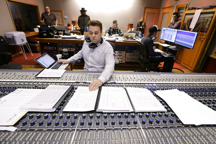 In this Oct. 21, 2019, photo, Nick Spezia works in the control room during the recording of a video game soundtrack in Nashville, Tenn. Music City is earning a new reputation as Soundtrack City. And more production companies, including Netflix, Showtime, Sony and Focus Features, have been lured to Nashville to record music for movies, TV and video games in the last year thanks to a new incentive program. (AP Photo/Mark Humphrey)