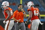 FILE - In this Sept. 10, 2020, file photo, Miami coach Manny Diaz, center, walks on the field during the team's NCAA college football game against UAB in Miami Gardens, Fla. Diaz's Hurricanes visit Duke on Saturday night in their first game since Nov. 14. (Al Diaz/Miami Herald via AP, File)