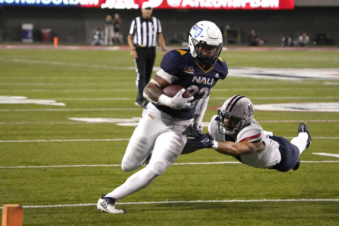 Northern Arizona running back Kevin Daniels (22) scores a touchdown despite the diving tackle attempt by Arizona safety Rhedi Short during the second half of an NCAA college football game Saturday, Sept. 18, 2021, in Tucson, Ariz. Northern Arizona won 21-19. (AP Photo/Rick Scuteri)
