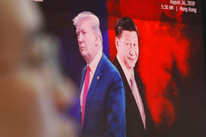 FIEL - In this Aug. 26, 2019, file photo, a computer screen shows images of Chinese President Xi Jinping, right, and U.S. President Donald Trump as a currency trader works at the foreign exchange dealing room of the KEB Hana Bank headquarters in Seoul, South Korea. China will lift punitive tariffs imposed on U.S. soybeans and pork in a trade war with Washington, a state news agency said Friday, Sept. 13, 2019, in a possible goodwill gesture ahead of negotiations. (AP Photo/Ahn Young-joon, File)