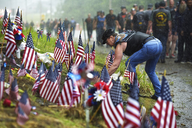 FILE - In this July 6, 2019, file photo, a woman views the memorial site for seven bikers who were killed in a collision while riding with the Jarheads Motorcycle Club June 2019, in Randolph, N.H. The National Transportation Safety Board found Tuesday, Dec. 1, 2020, a pickup driver's drug use was the reason he crashed last year into the oncoming group of motorcyclists in New Hampshire, leading to the death of the bikers.   (Paul Hayes/Caledonian-Record via AP, File)