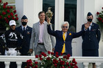 Trainer Bob Baffert holds the trophy after John Velazquez, left, rode Authentic to victory in the 146th running of the Kentucky Derby at Churchill Downs, Saturday, Sept. 5, 2020, in Louisville, Ky. (AP Photo/Jeff Roberson)