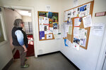In this Wednesday, May 6, 2020, photo, postmistress Stephanie Black scans the bulletin board to make sure only non-profit messages are posted at the Deer Isle, Maine post office. From coastal Maine to Philadelphia's close-knit neighborhoods, many residents call the service essential to their communities. (AP Photo/Robert F. Bukaty)