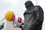 A blimp balloon depicting contender for leadership of Britain's ruling Conservative Party, Boris Johnson is launched outside Parliament, next to a statue of wartime leader Winston Churchill, during an anti-Brexit protest in London, Saturday July, 20, 2019. The pro-European march was organised by the March for Change group. Johnson is a leading Brexit advocate. (Aaron Chown/PA via AP)