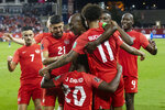 Canada's captain Atiba Hutchinson stands in the center of the celebrations as the team celebrates their third goal against El Salvador during the second half of a World Cup qualifying soccer match Wednesday, Sept. 8, 2021, in Toronto. (Chris Young/The Canadian Press via AP)