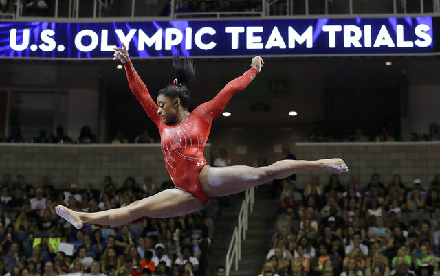 FILE - In this July 10, 2016, file photo, Simone Biles competes on the balance beam during the women's U.S. Olympic gymnastics trials in San Jose, Calif. At least 70 percent of U.S. Olympic sports organizations have applied for government loans in the coronavirus pandemic, underscoring the frailties within the world's most dominant Olympic sports system. (AP Photo/Gregory Bull, File)