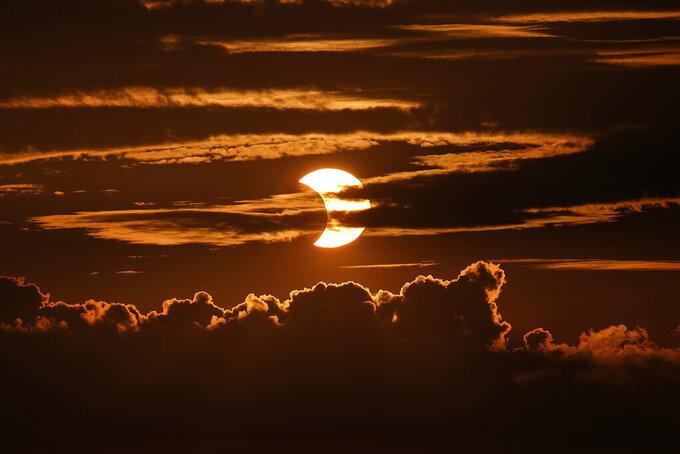 A partial solar eclipse rises behind clouds, Thursday, June 10, 2021, in Arbutus, Md. (AP Photo/Julio Cortez)