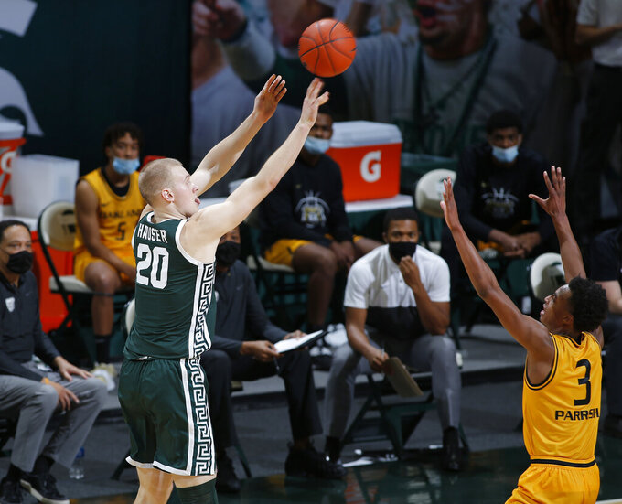 Michigan State's Joey Hauser, left, shoots against Oakland's Micah Parrish (3) during the first half of an NCAA college basketball game, Sunday, Dec. 13, 2020, in East Lansing, Mich. (AP Photo/Al Goldis)