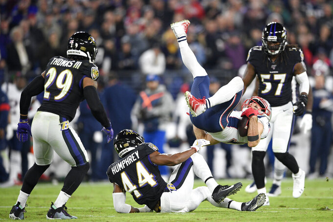 New England Patriots wide receiver Julian Edelman, right, flips over after a hit as Baltimore Ravens safety Earl Thomas III (29), cornerback Marlon Humphrey (44) and linebacker Josh Bynes (57) look on during the first half of an NFL football game, Sunday, Nov. 3, 2019, in Baltimore. (AP Photo/Nick Wass)
