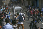 FILE - In this Friday, June 1, 2018, file photo, Kashmiri Protesters attack an Indian paramilitary vehicle in Srinagar, Indian controlled Kashmir. The death of top separatist leader Syed Ali Geelani on Sept. 1, 2021, in disputed Kashmir and the ensuing crackdown on public movement and communications by Indian authorities have highlighted the turmoil seething just below the surface in the region. Soon after the 92-year-old's death late Wednesday, authorities quickly clamped down, blocking internet and mobile phone services and restricting public movement out of fear of anti-India protests. (AP Photo/Dar Yasin, File)