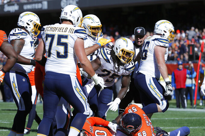 Los Angeles Chargers running back Melvin Gordon (25) celebrates with teammates after scoring on a 19-yard touchdown run during the first half of an NFL football game against the Chicago Bears, Sunday, Oct. 27, 2019, in Chicago. (AP Photo/Charles Rex Arbogast)