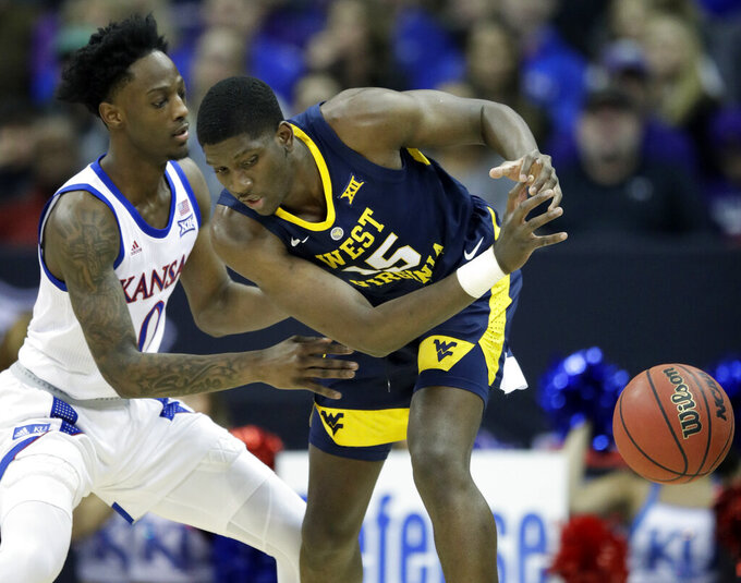 Kansas guard Marcus Garrett (0) knocks the ball away from West Virginia forward Lamont West (15) during the first half of an NCAA college basketball game in the semifinals of the Big 12 conference tournament in Kansas City, Mo., Friday, March 15, 2019. (AP Photo/Orlin Wagner)