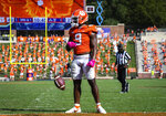 Clemson running back Travis Etienne (9) spins the ball out of his hands after scoring a touchdown during an NCAA college football game against Syracuse in Clemson, S.C., on Saturday, Oct. 24, 2020. (Ken Ruinard/Pool Photo via AP)