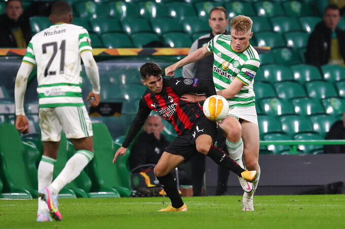 AC Milan's Brahim Diaz, center and Celtic's Stephen Welsh, right, fight for the ball during the Europa League Group H first leg soccer match between Celtic and AC Milan at the Celtic Park stadium in Glasgow, Scotland, Thursday, Oct. 22, 2020. (Jane Barlow/Pool via AP)