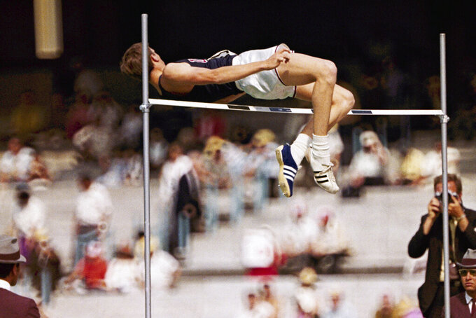 """FILE - In this 1968 file photo, Dick Fosbury, of the United States, clears the bar in the high jump competition at the 1968 Mexico City Olympics. Fosbury is celebrated for the """"Fosbury Flop,"""" which revolutionized high-jumping. As he clears the bar he twists his body so that he goes over the bar head first which his back to the bar. The Mexico City audience was captivated by Fosbury and shouted, """"Ole"""" as he cleared the bar. (AP Photo/File)"""