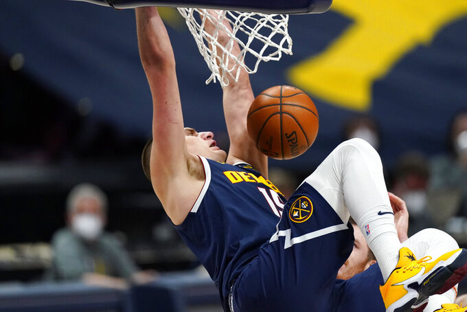 Denver Nuggets center Nikola Jokic hangs from the rim after dunking against the San Antonio Spurs in the second half of an NBA basketball game Friday, April 9, 2021, in Denver. (AP Photo/David Zalubowski)