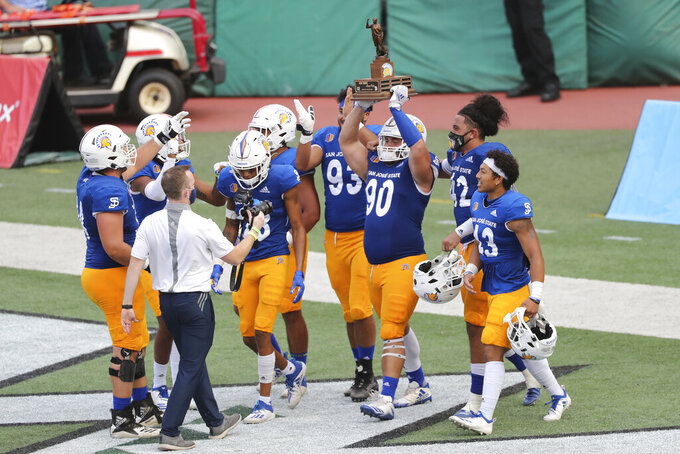San Jose State football players hold the Dick Tomey Legacy Trophy after defeating Hawaii in an NCAA college football game Saturday, Dec. 5, 2020, in Honolulu. (AP Photo/Marco Garcia)