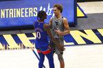Kansas guard Marcus Garrett (0) and West Virginia forward Emmitt Matthews Jr. (11) greet each other after West Virginia wins during the second half of an NCAA college basketball game Saturday, Feb. 6, 2021, in Morgantown, W.Va. (AP Photo/Kathleen Batten)